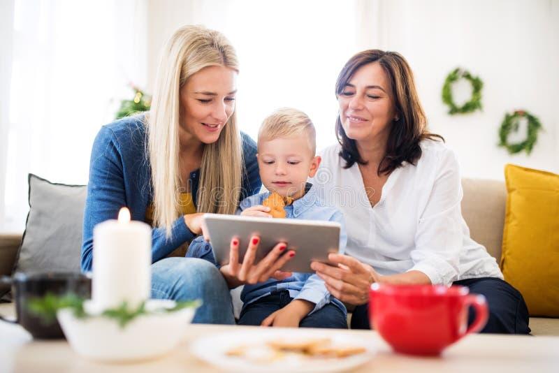 Un petit garçon avec la mère et la grand-mère à la maison au temps de Noël, utilisant le comprimé images stock