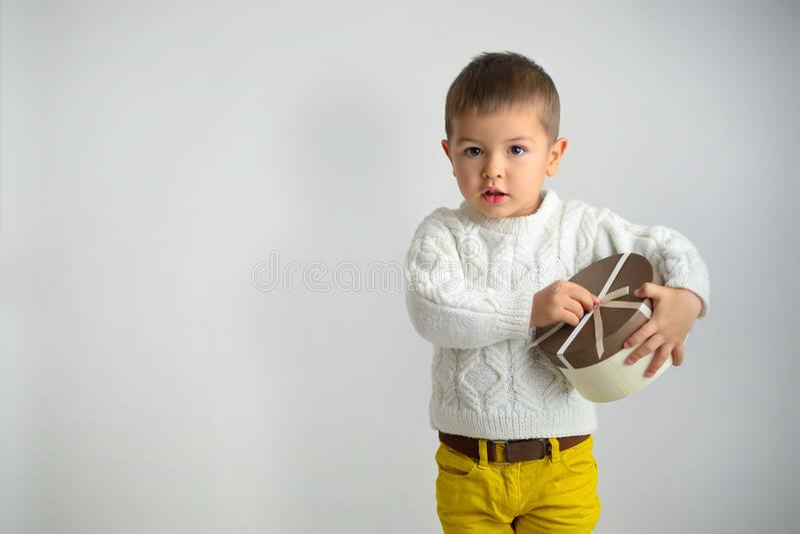 Un petit garçon déliant un ruban sur un cadeau de boîte en carton Isolat o photographie stock