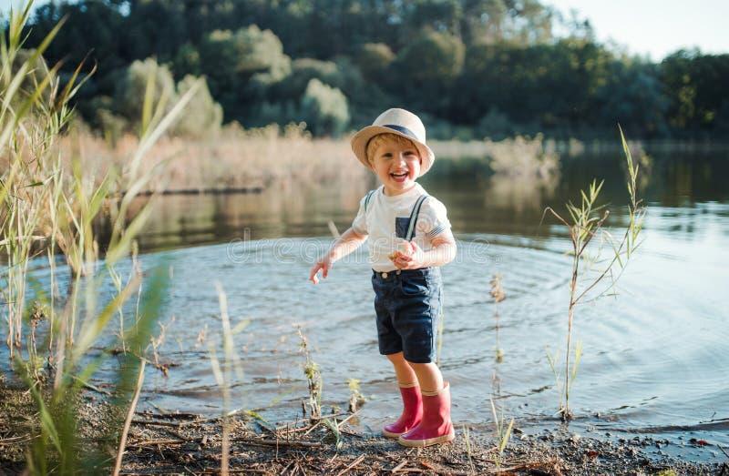 Un petit garçon d'enfant en bas âge se tenant prêt un lac, mangeant une pomme image stock