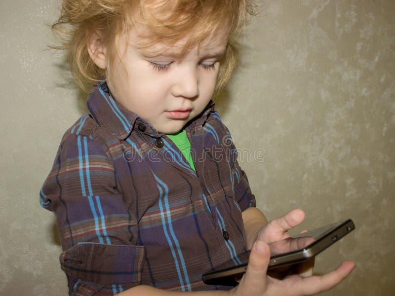 Un petit garçon d'enfant en bas âge tient un instrument dans des ses mains et clique sur dessus l'écran de smartphone photos stock