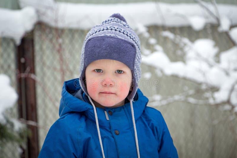 Un petit garçon dans un chapeau et une veste d'hiver tout en marchant un jour neigeux d'hiver froid image stock