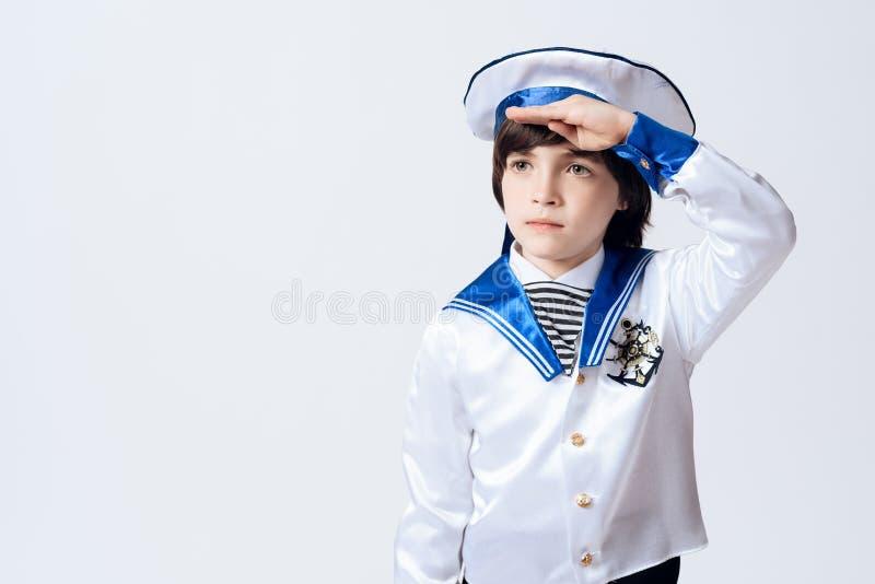 Un petit garçon dans le costume d'un marin Le garçon aux cheveux foncés dans le costume a salué photo stock