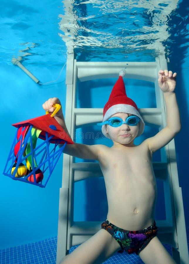 Un petit garçon dans un chapeau Santa Claus avec un cadeau s'assied à disposition sous l'eau sur les escaliers au fond de la pisc photographie stock