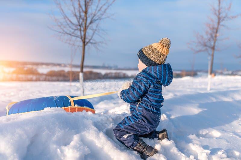 Un petit gar?on de 3 ann?es, en hiver sur la rue tire une tuyauterie, pour skier d'une colline, jouant ayant l'amusement d?tendan images stock