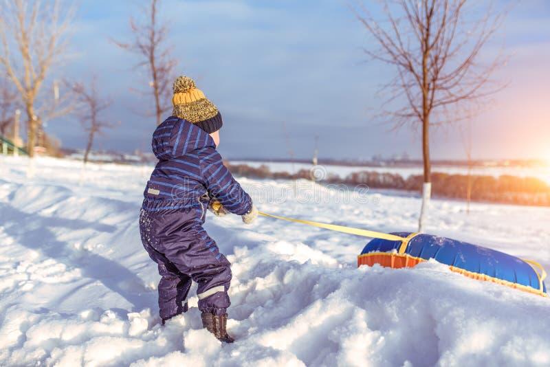 Un petit garçon de 3-4 années, tire une tuyauterie gonflable de jouet pour skier de la glissière en hiver dehors, fond photos stock