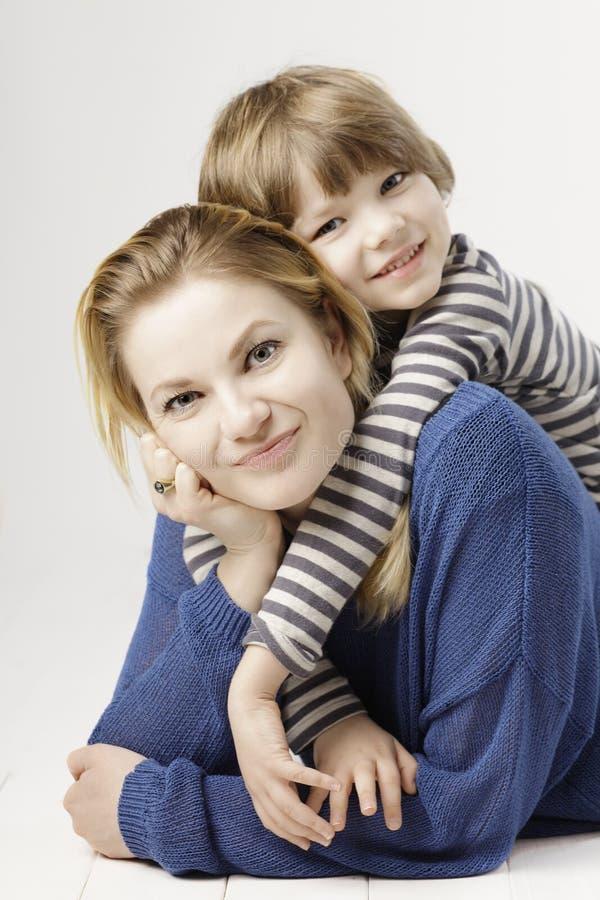 Un petit garçon de sourire et sa mère étreignant sur le fond blanc photographie stock libre de droits