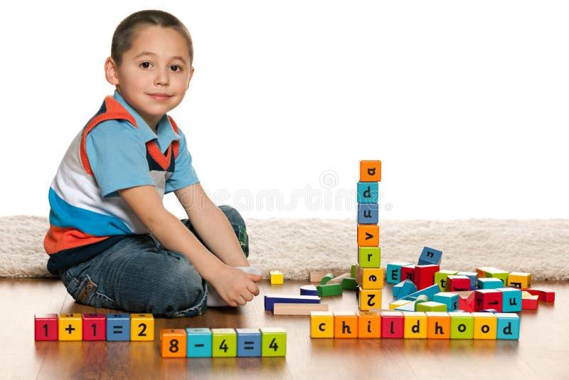 Jeu avec garçon de sourire de jouets le petit photo libre de droits