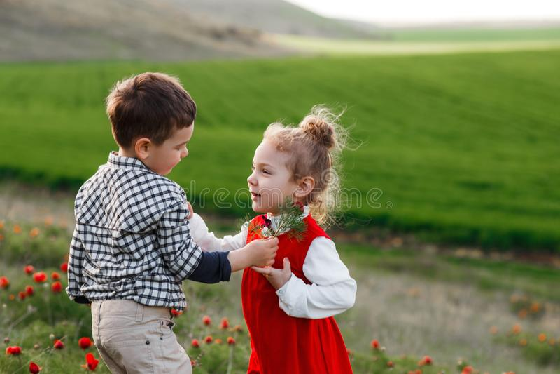 Un petit garçon donnant des fleurs à une fille Le concept de l'amour photos stock