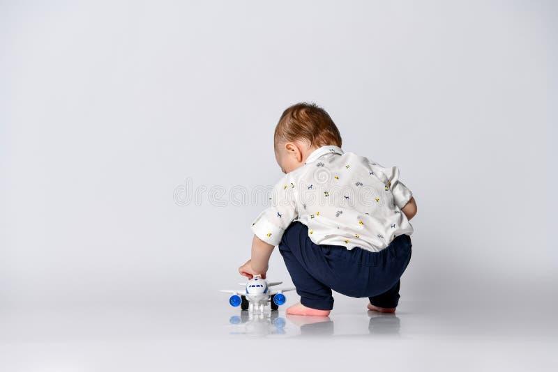 Un petit garçon en bas âge s'assied sur un fond de mur clair dans une pièce vide avec un avion en peluche photos libres de droits