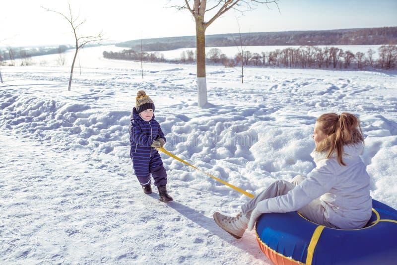 Un petit garçon, un fils de 2 ou 3 années, traîne une ceinture de tuyauterie derrière une corde, une mère se repose sur une femme photographie stock libre de droits