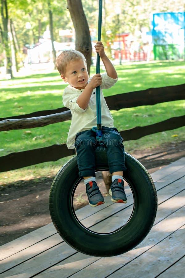 Un petit garçon habillé dans un T-shirt blanc et des jeans monte une oscillation faite d'un pneu de voiture en parc d'été images stock
