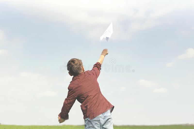 Un petit garçon jetant un avion de papier dans le ciel photos libres de droits