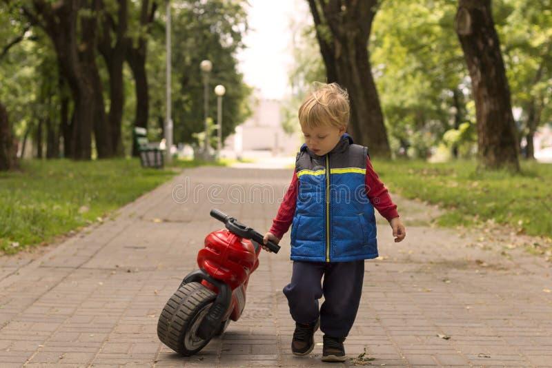 Un petit garçon jouant à l'extérieur avec une motocyclette en plastique de jouet images libres de droits