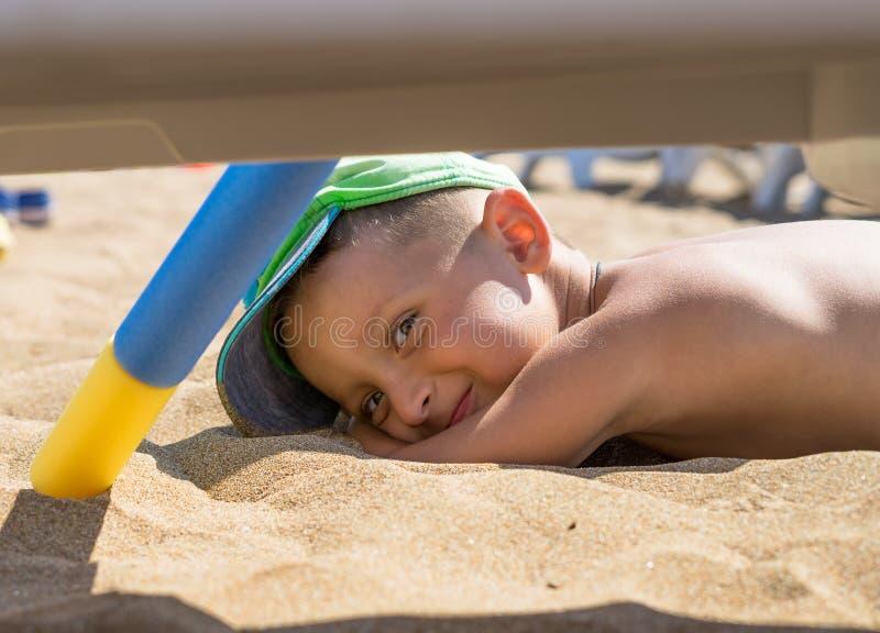 Un petit garçon joue dans le sable sur la mer, les petites jambes et les doigts, à un maillot de bain, à un arrière-plan de W à s photos stock