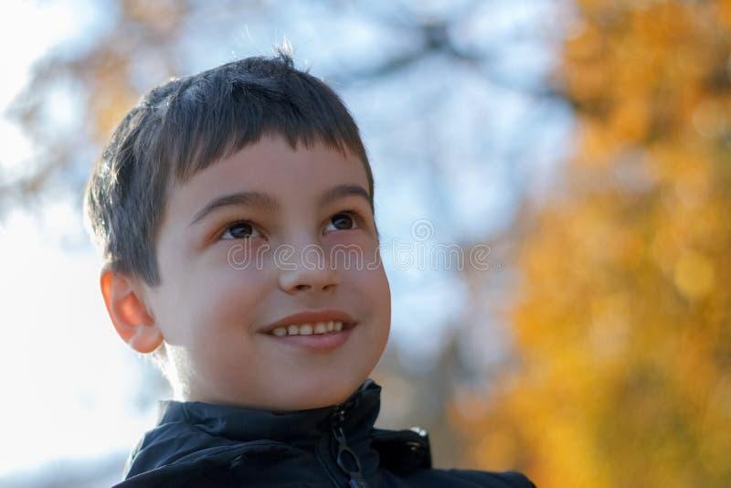 Un petit garçon marche en parc d'automne, un écolier en parc d'automne dans des feuilles jaunes photographie stock libre de droits