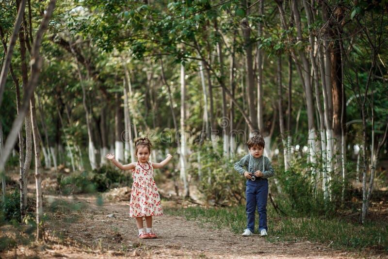 Un petit garçon mignon dans des vêtements de cru et une petite belle fille dans une rétro robe marchent dans les bois et prennent photographie stock