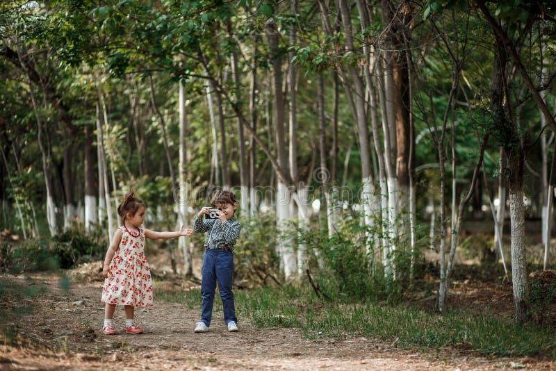 Un petit garçon mignon dans des vêtements de cru et une petite belle fille dans une rétro robe marchent dans les bois et prennent photos libres de droits
