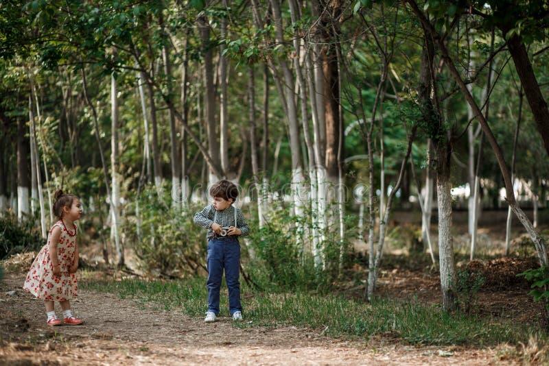 Un petit garçon mignon dans des vêtements de cru et une petite belle fille dans une rétro robe marchent dans les bois et prennent image libre de droits