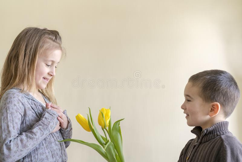 Un petit garçon mignon donne des fleurs à une fille qui est plus âgée que lui Le concept de l'amour et de l'amitié photo stock