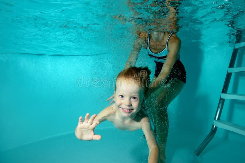 Un petit garçon plonge sous l'eau et nage à l'appareil-photo, et sa mère l'assure image stock