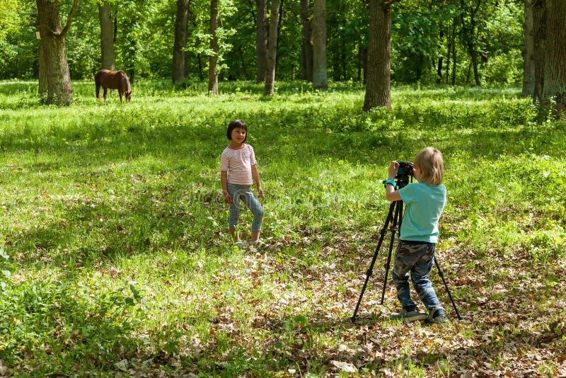 Un petit garçon prend à des photos un gir photographie stock