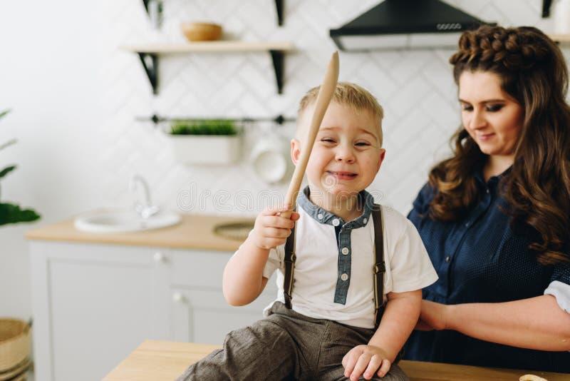 Un petit garçon s'asseyant sur la table de cuisine et jouant avec un outil de cuisine et souriant heureusement avec sa mère derri photo stock