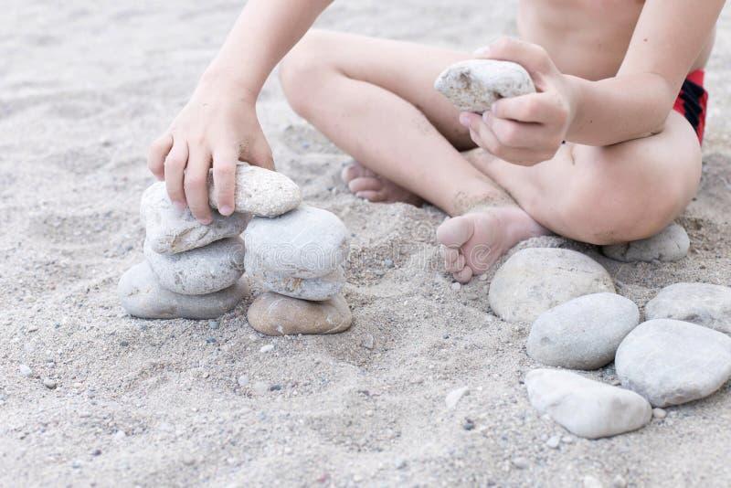 Un petit garçon s'asseyant sur le sable faisant la tour à partir des pierres photos stock