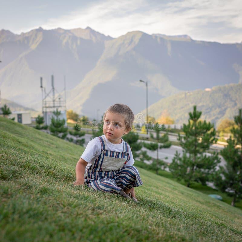 Un petit garçon s'asseyant sur une pente verte image libre de droits