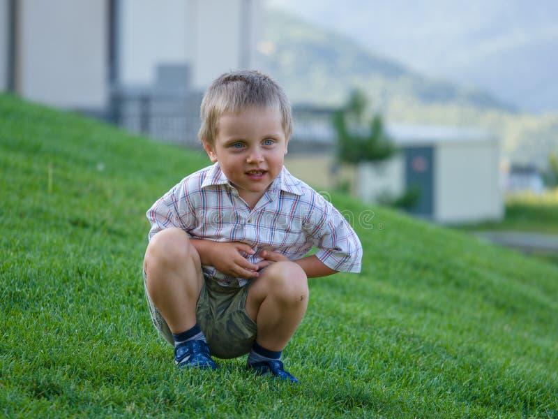 Un petit garçon s'asseyant sur une pente verte photos stock