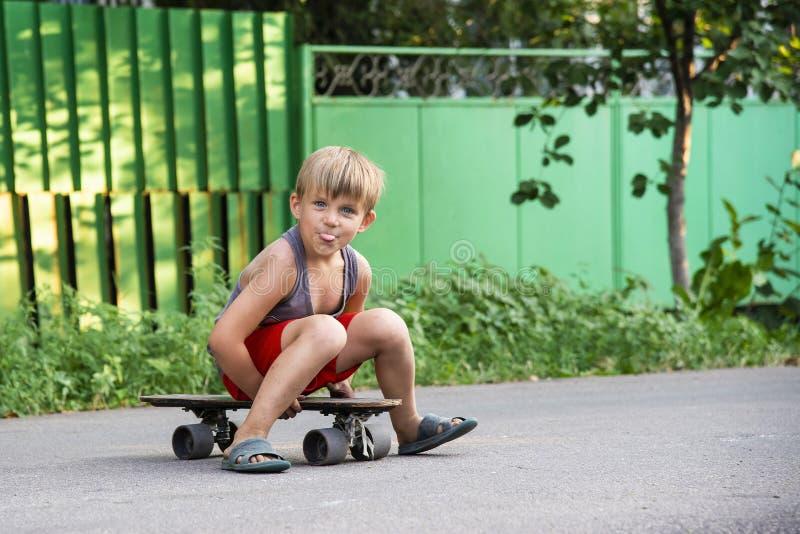 Un petit garçon s'assied sur une planche à roulettes près de la maison sur la route image libre de droits