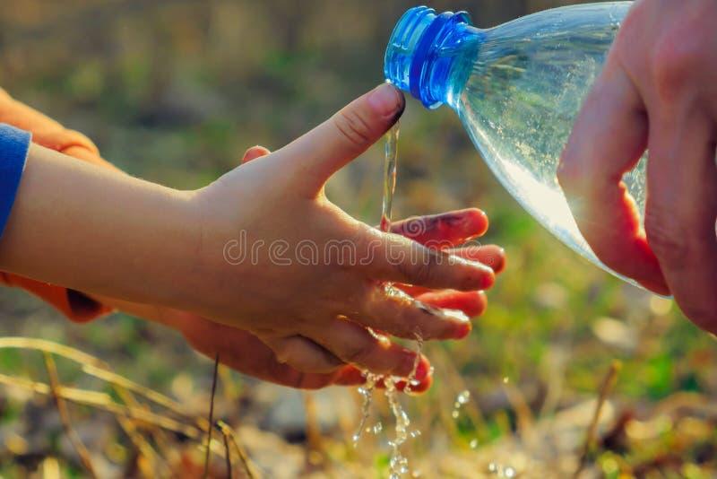 Un petit garçon se lave les mains sur un pique-nique avec sa mère Hygiène extérieure avant la consommation photographie stock