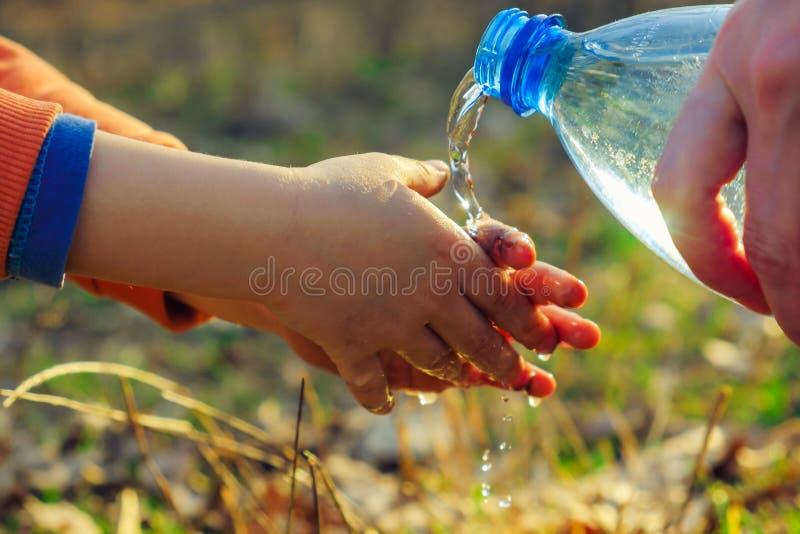 Un petit garçon se lave les mains sur un pique-nique avec sa mère Hygiène extérieure avant la consommation image stock