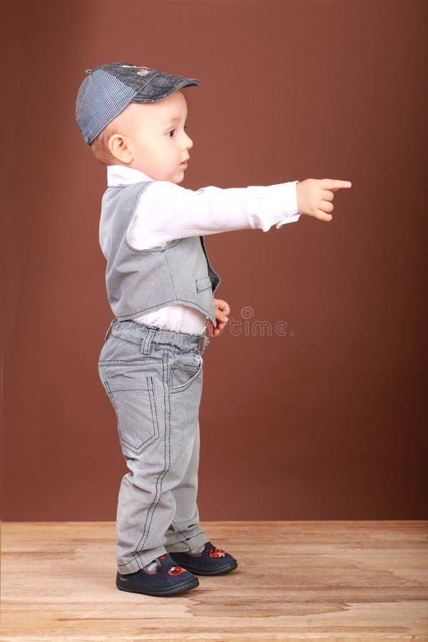 Un petit garçon se tient en longueur à l'appareil-photo et montre en avant image libre de droits