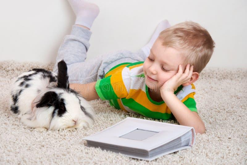 Un petit garçon se trouve sur le tapis avec son lapin aimé et choie son animal familier photographie stock libre de droits