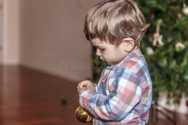 Un petit garçon tient dans des ses mains une boule décorative d'or photographie stock libre de droits