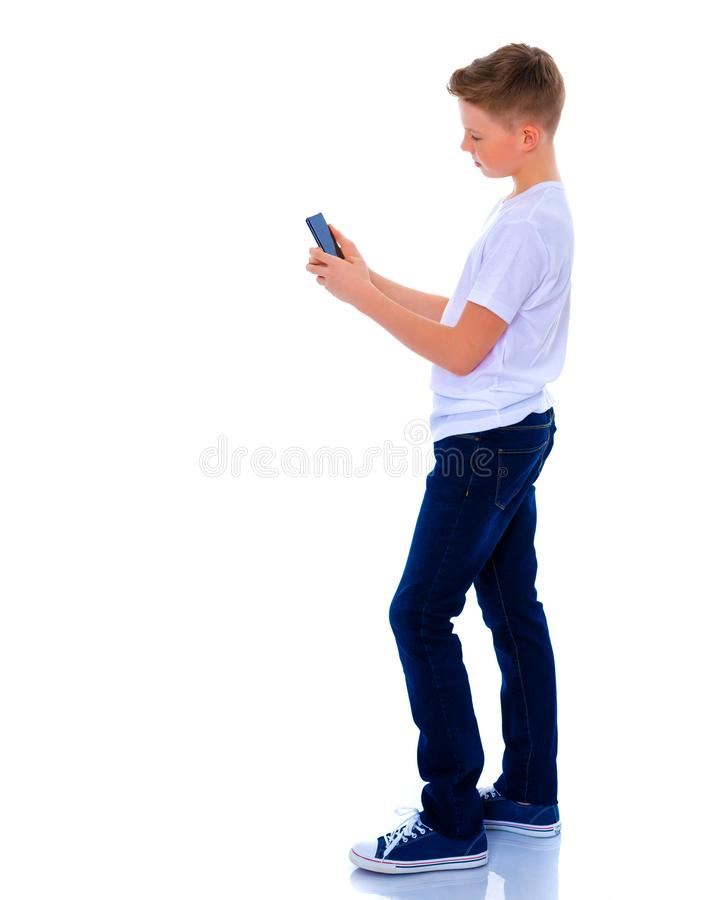 Un petit garçon utilise un téléphone portable photographie stock