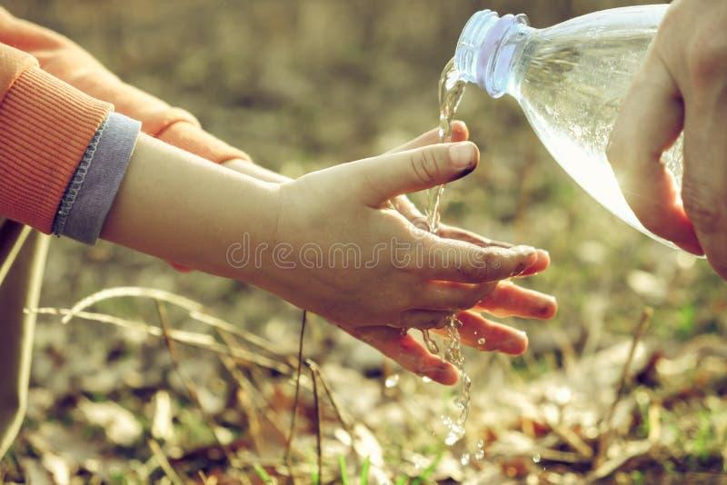 Un petit gar?on se lave les mains sur un pique-nique avec sa m?re Hygi?ne ext?rieure avant la consommation images stock