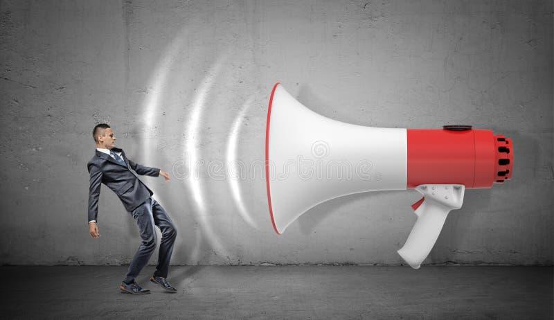 Un petit homme d'affaires est enlevé à l'air comprimé par les ondes sonores venant d'un mégaphone géant photo stock