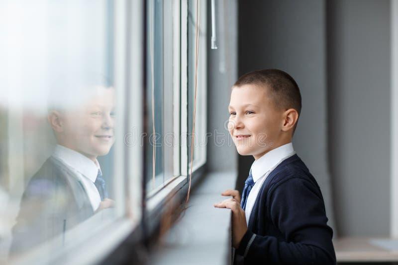 Un petit homme d'affaires regarde par la fenêtre de son bureau image libre de droits