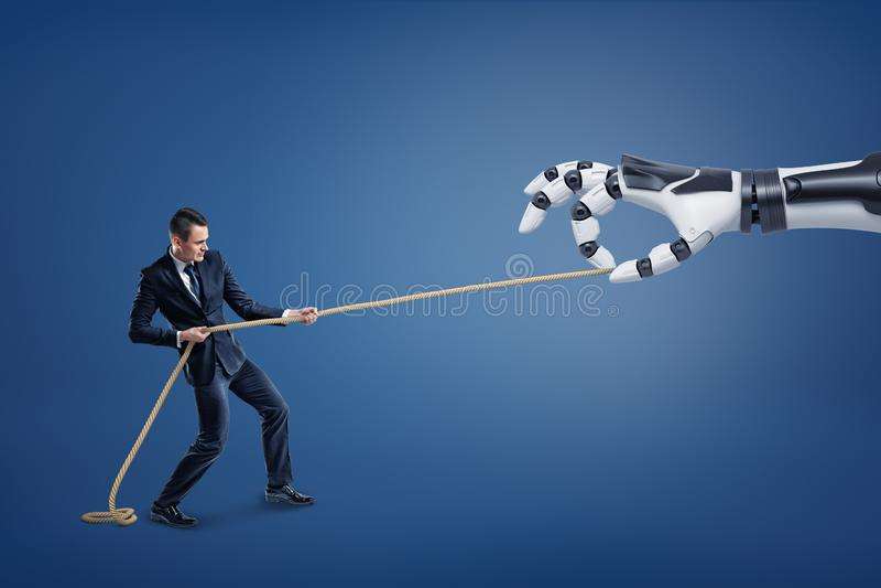 Un petit homme d'affaires tire une longue corde avec effort concurrençant une main robotique géante photos stock