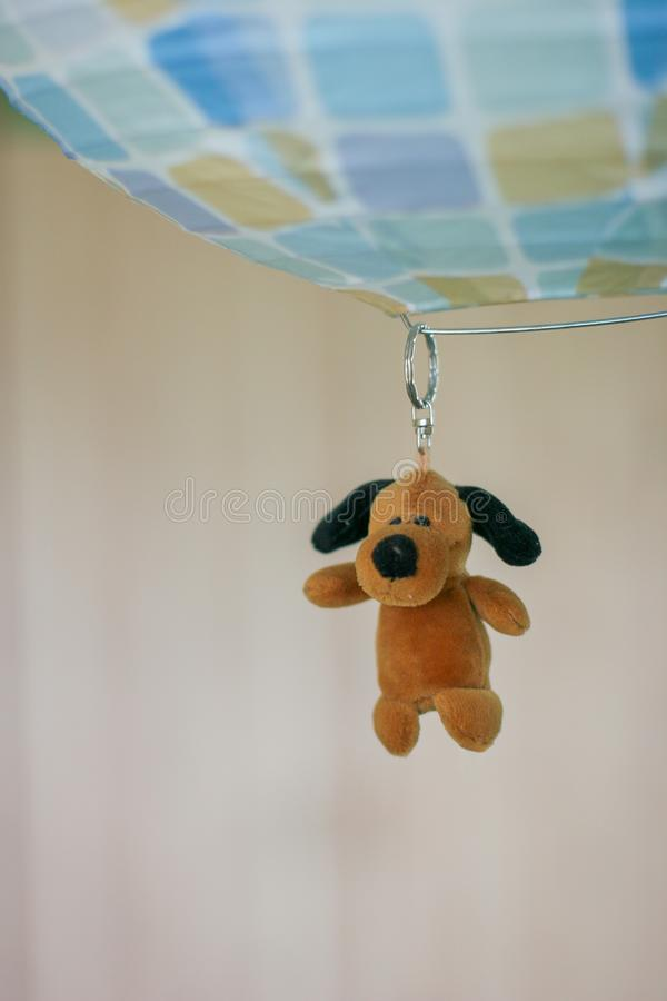 Un petit keychain brun de chienchien avec les oreilles, les yeux et le nez noirs accroche sur l'anneau sur la boule photographie stock