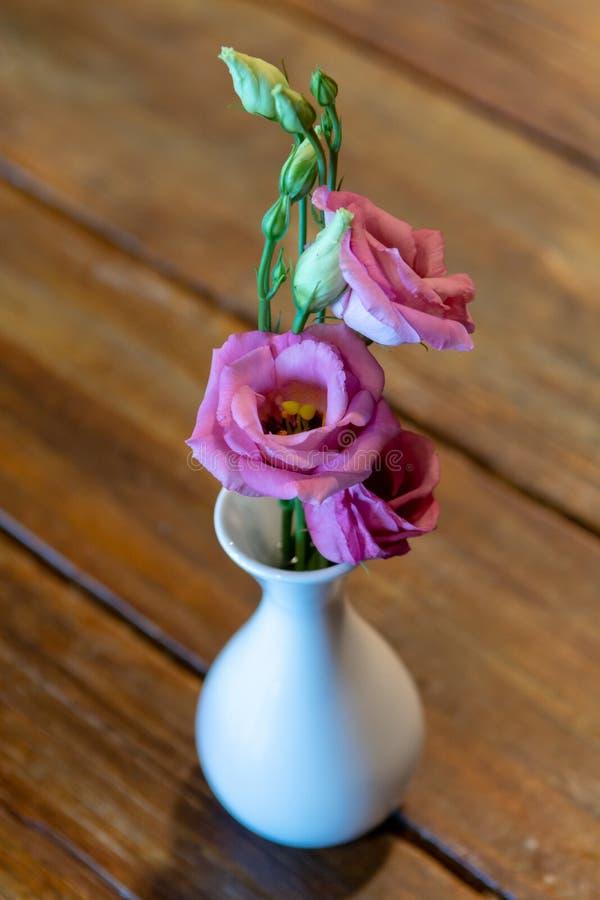 Un petit mini vase blanc avec la fleur rose sur la table en bois photographie stock libre de droits