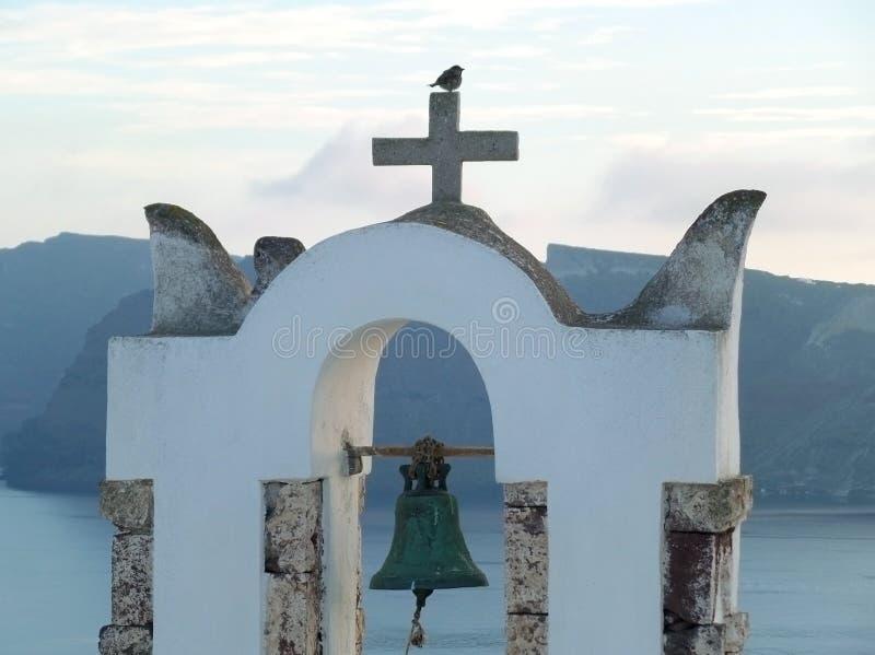 Un petit moineau étant perché sur la croix d'une tour de cloche blanche d'église avant coucher du soleil, île de Santorini photos libres de droits