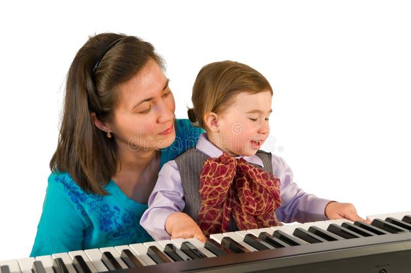 Un petit petit garçon jouant le piano. images libres de droits