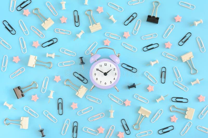 Un petit réveil lilas, au centre de la pagaille des fournitures de bureau Trombones blancs et noirs, de secrétaire image libre de droits