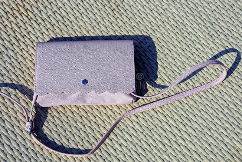 Un petit sac à main en cuir rose sur une table grise photo stock