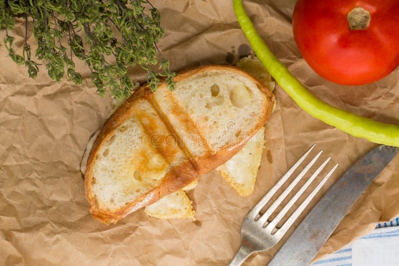 Un petit sandwich avec du fromage, une tomate et un poivre frais vert image libre de droits