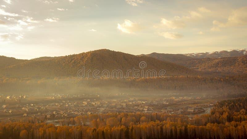 Un petit village enveloppé en brume mince pendant le début de la matinée images stock