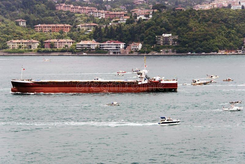 Un petrolero grande y porciones de pequeños barcos de pesca en Estambul imagen de archivo