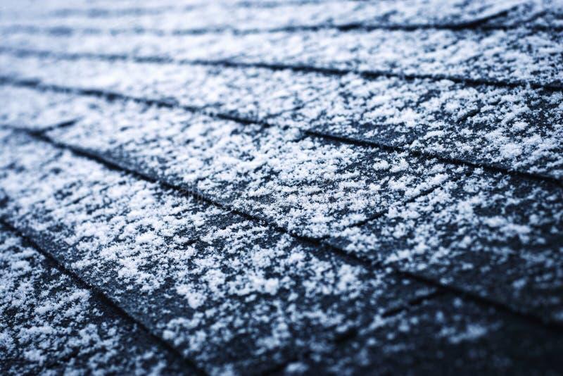 Un peu de neige sur des bardeaux d'asphalte photographie stock